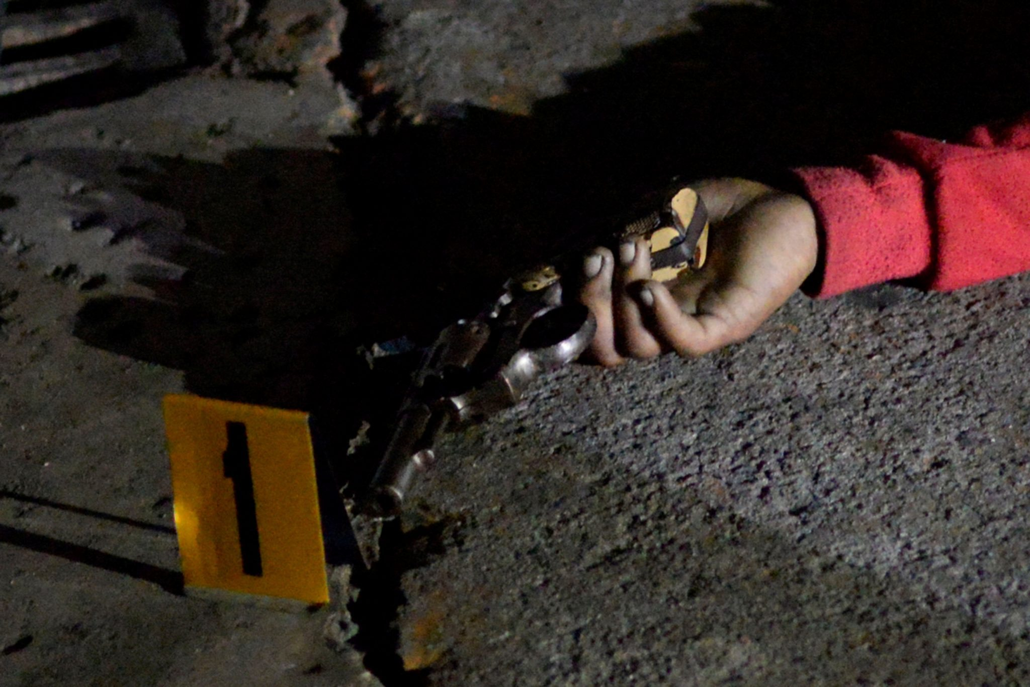 A revolver in the hand of one of the three bodies of men lying on a street, who police said were gunned down in an armed encounter by policemen at a police checkpoint in Manila, Philippines September 21, 2016 / REUTERS