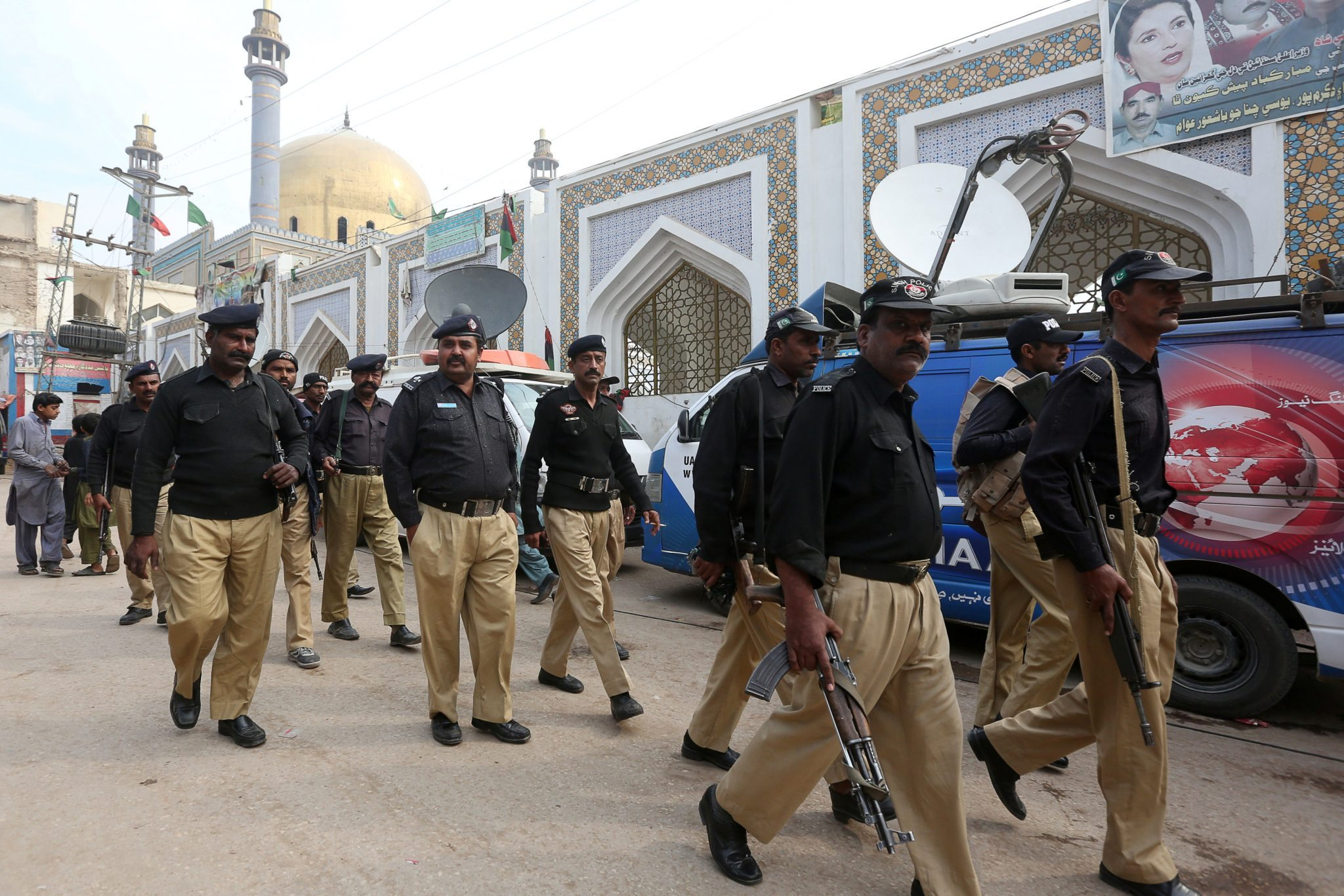 Policemen gather outside the tomb of Sufi saint Syed Usman Marwan after Thursday's suicide blast | REUTERS