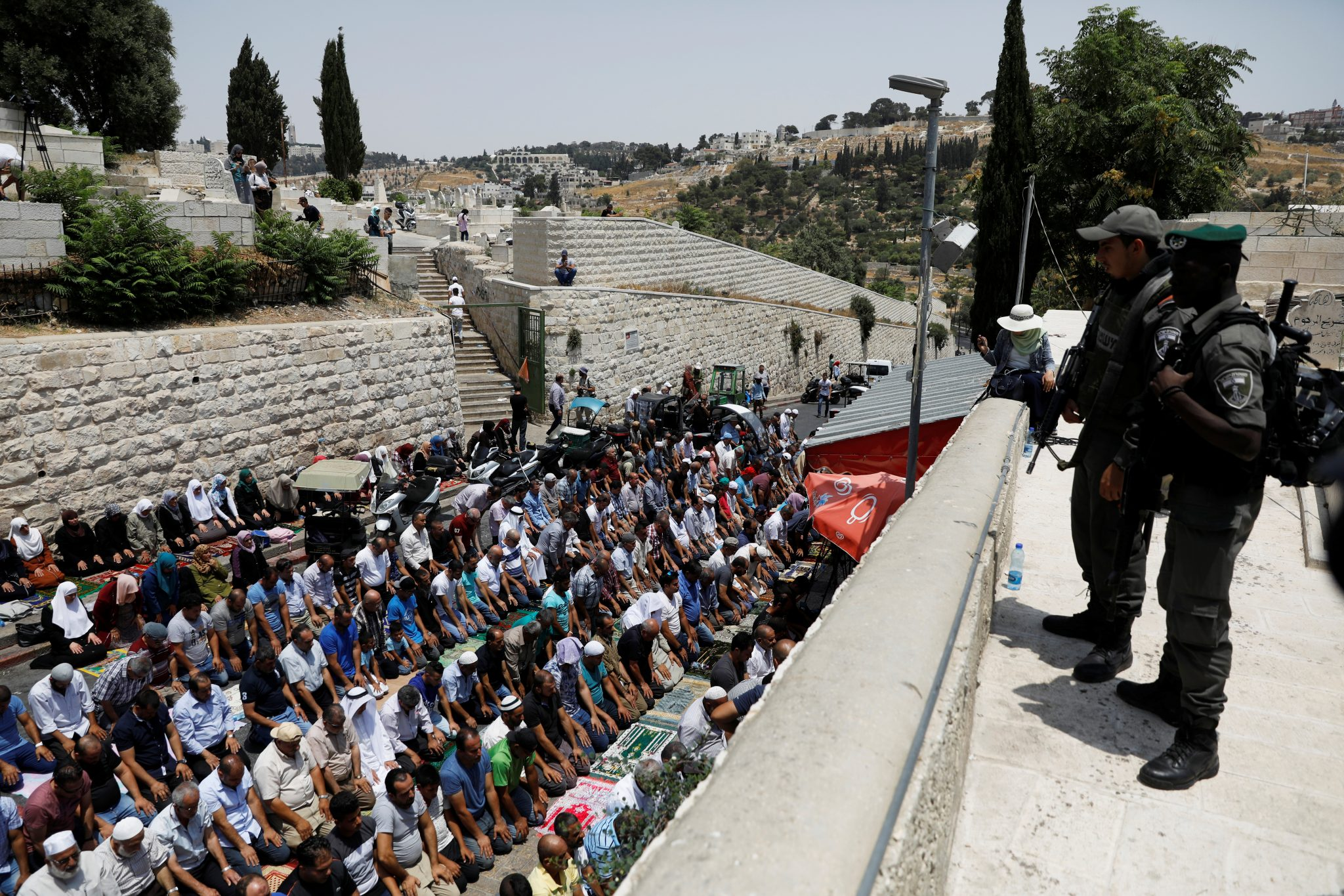 Israeli border police officers stand guard as Palestinians pray at Lions' Gate, the entrance to Jerusalem's Old City, in protest over Israel's new security measures at the compound housing al-Aqsa mosque | REUTERS