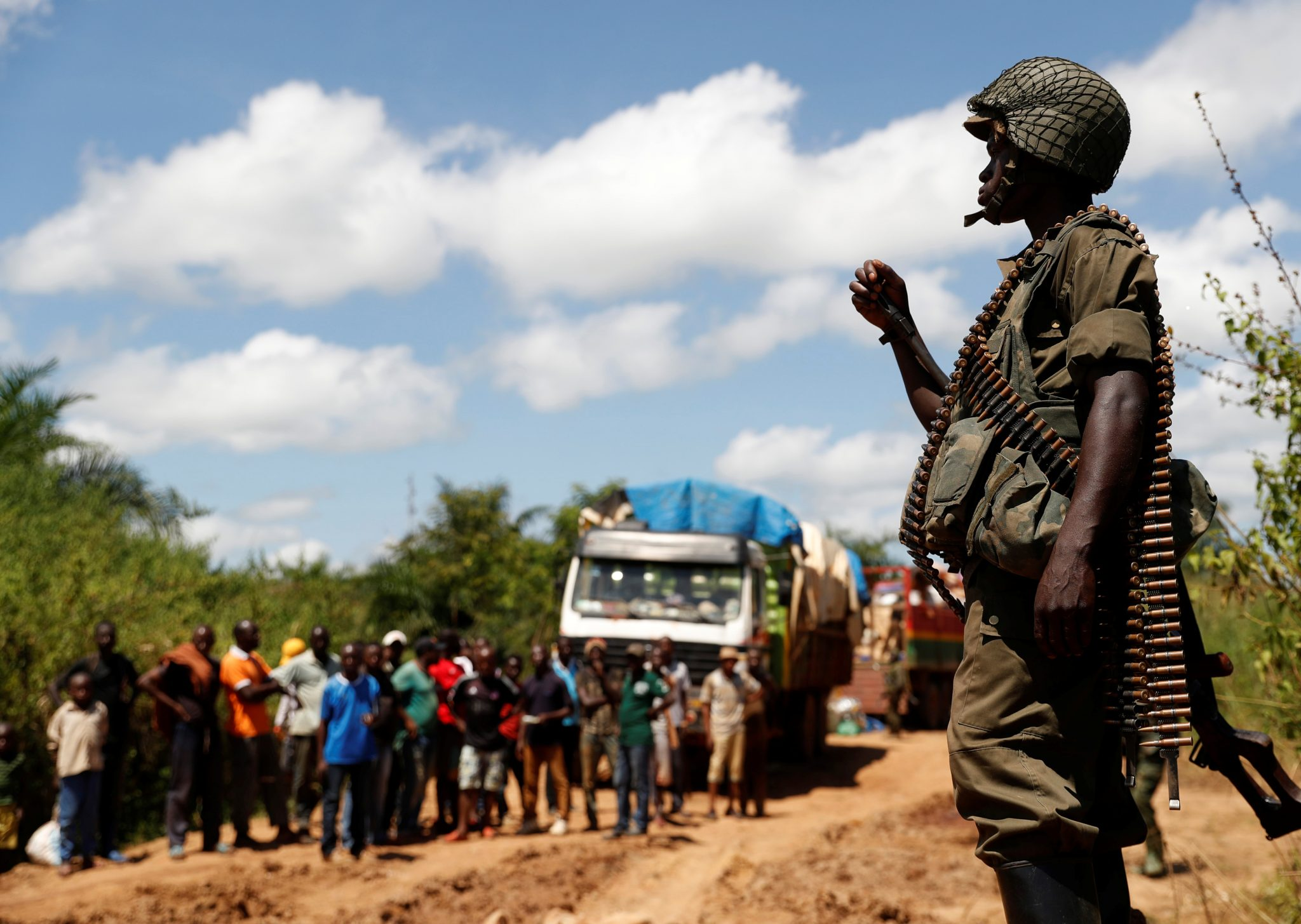 A Congolese soldier from the Armed Forces of the Democratic Republic of Congo (FARDC) stands in front of trucks who are stuck because of mud on the road as he searches with other soldiers for Mai-Mai Yakutumba rebels in Namoya, Maniema Province, eastern Democratic Republic of the Congo, April 29, 2018 | REUTERS