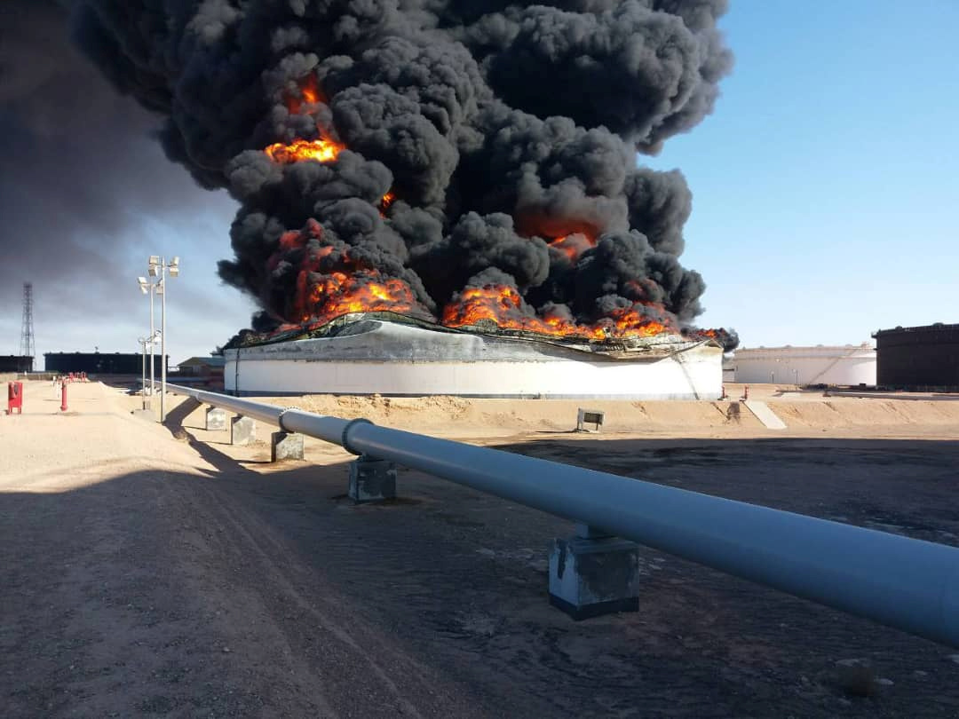 Smoke and flame rise from an oil storage tank that was set on fire amid fighting between rival factions at Ras Lanuf terminal, Libya in this handout picture released on June 18, 2018. | REUTERS