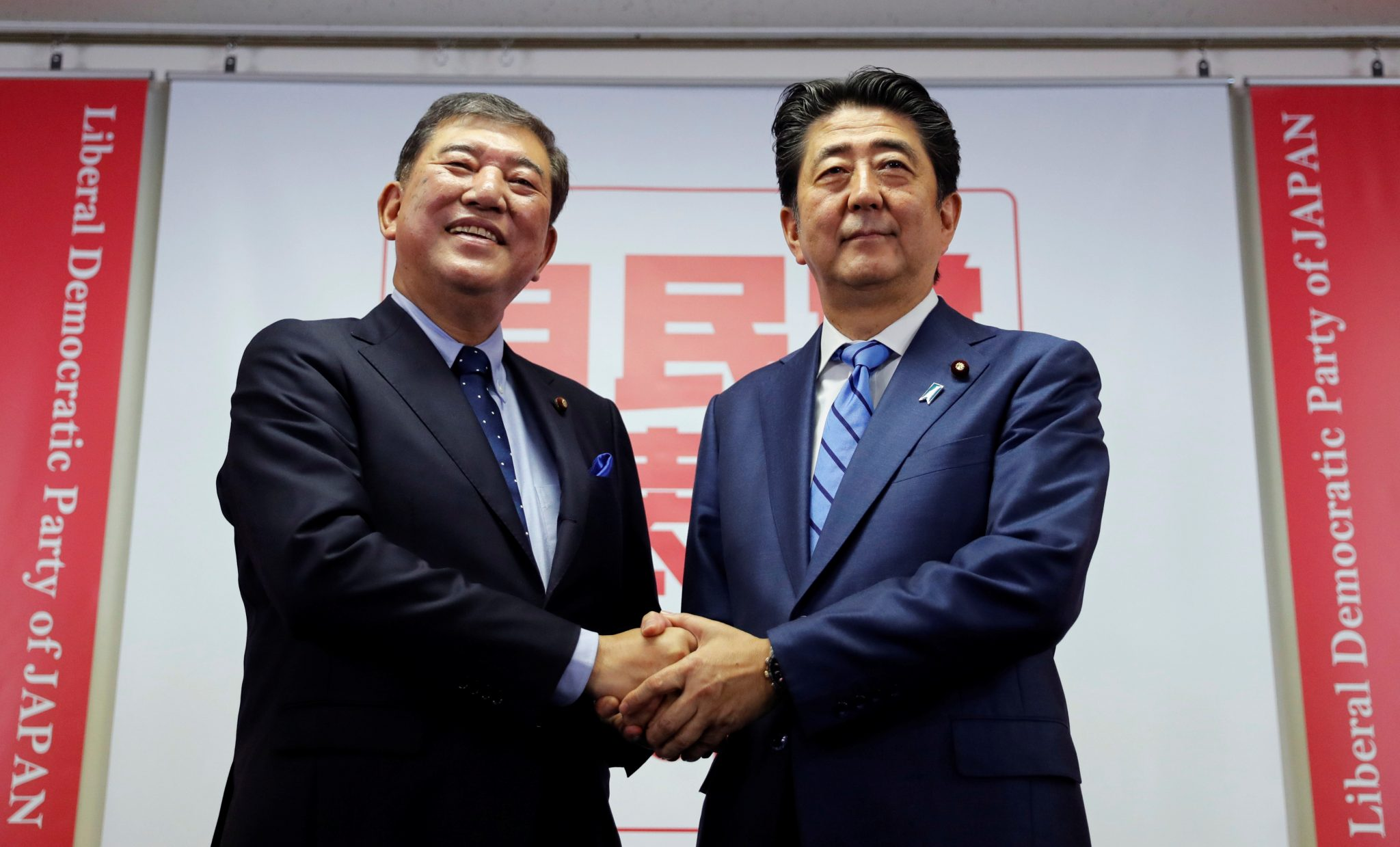 Japan's Prime Minister Shinzo Abe, who is also the ruling Liberal Democratic Party (LDP) leader, and ex-defence minister Shigeru Ishiba shake hands at the start of their joint news conference for the party leader election at the party's headquarters in Tokyo, Japan September 10, 2018. REUTERS/Toru Hanai - RC14D2444010