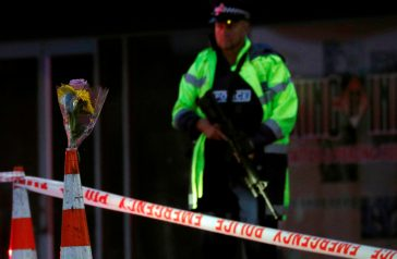 An armed police officer stands guard next to flowers offered by a resident outside Linwood mosque after Friday's gunmen attacks, in Christchurch, New Zealand March 16, 2019. REUTERS/Edgar Su - RC1FF1E1B160