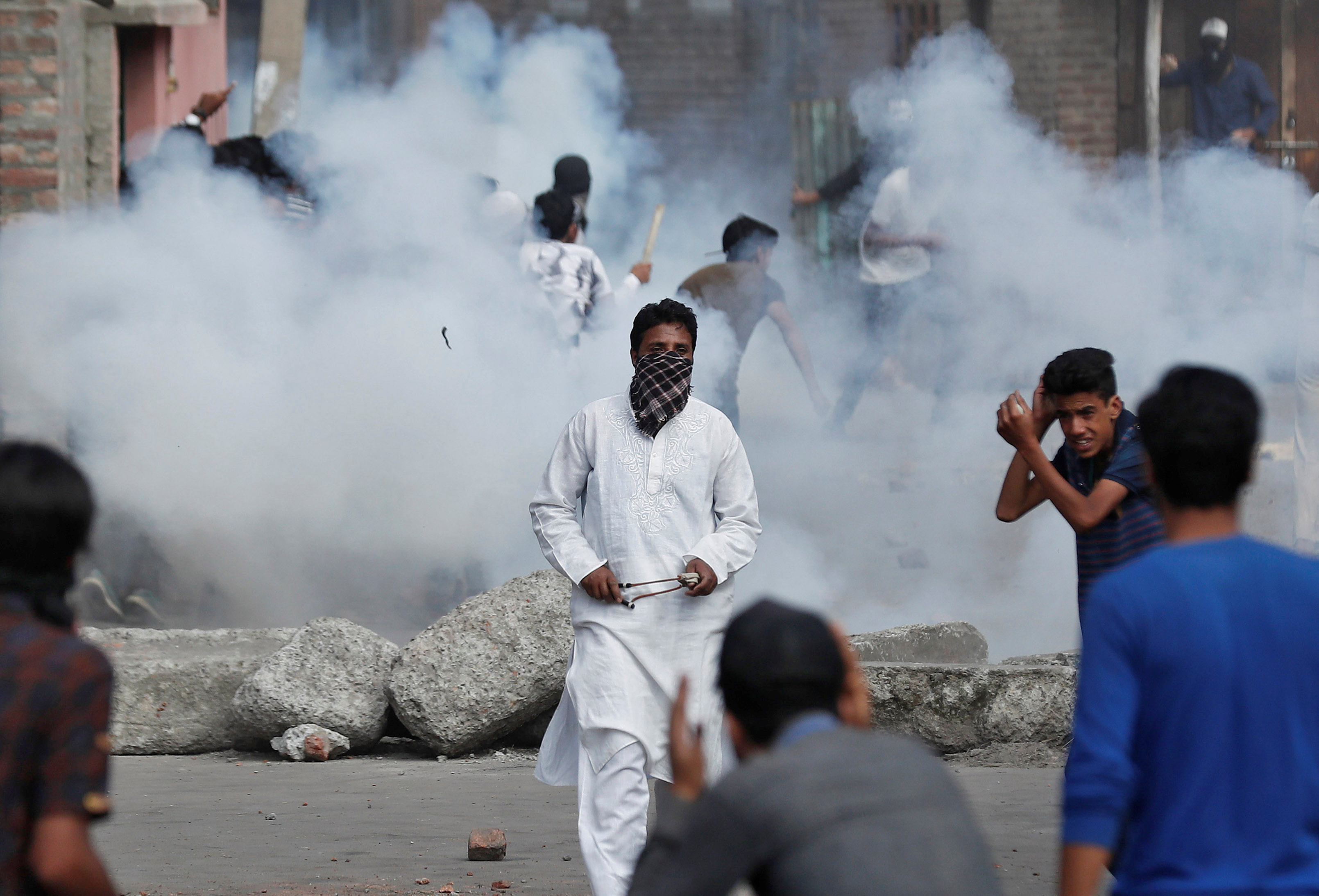 Kashmiris run for cover as smoke rises from teargas shells fired by Indian security forces during clashes, after scrapping of the special constitutional status for Kashmir by the Indian government, in Srinagar, August 23, 2019. REUTERS/Adnan Abidi - RC1E8E32D200