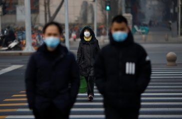People wearing masks walk across a street as the country is hit by an outbreak of the new coronavirus, in Beijing, China January 28, 2020. REUTERS/Carlos Garcia Rawlins - RC2ZOE97ASFV