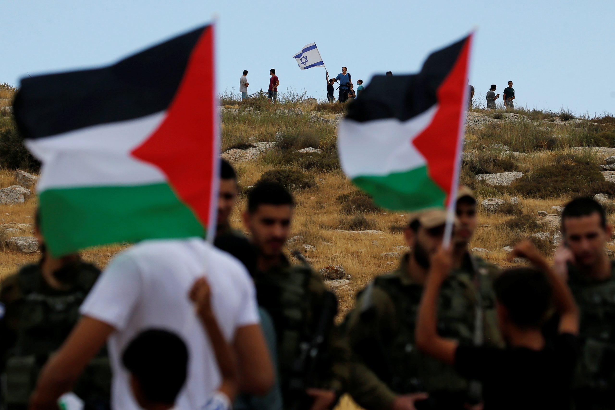 A Jewish settler holds an Israeli flag as Palestinians argue with Israeli soldiers during a protest against Israel's plan to annex parts of the occupied West Bank, in Susya village south of Heron June 19, 2020. REUTERS/Mussa Qawasma - RC2BCH9JZFXN